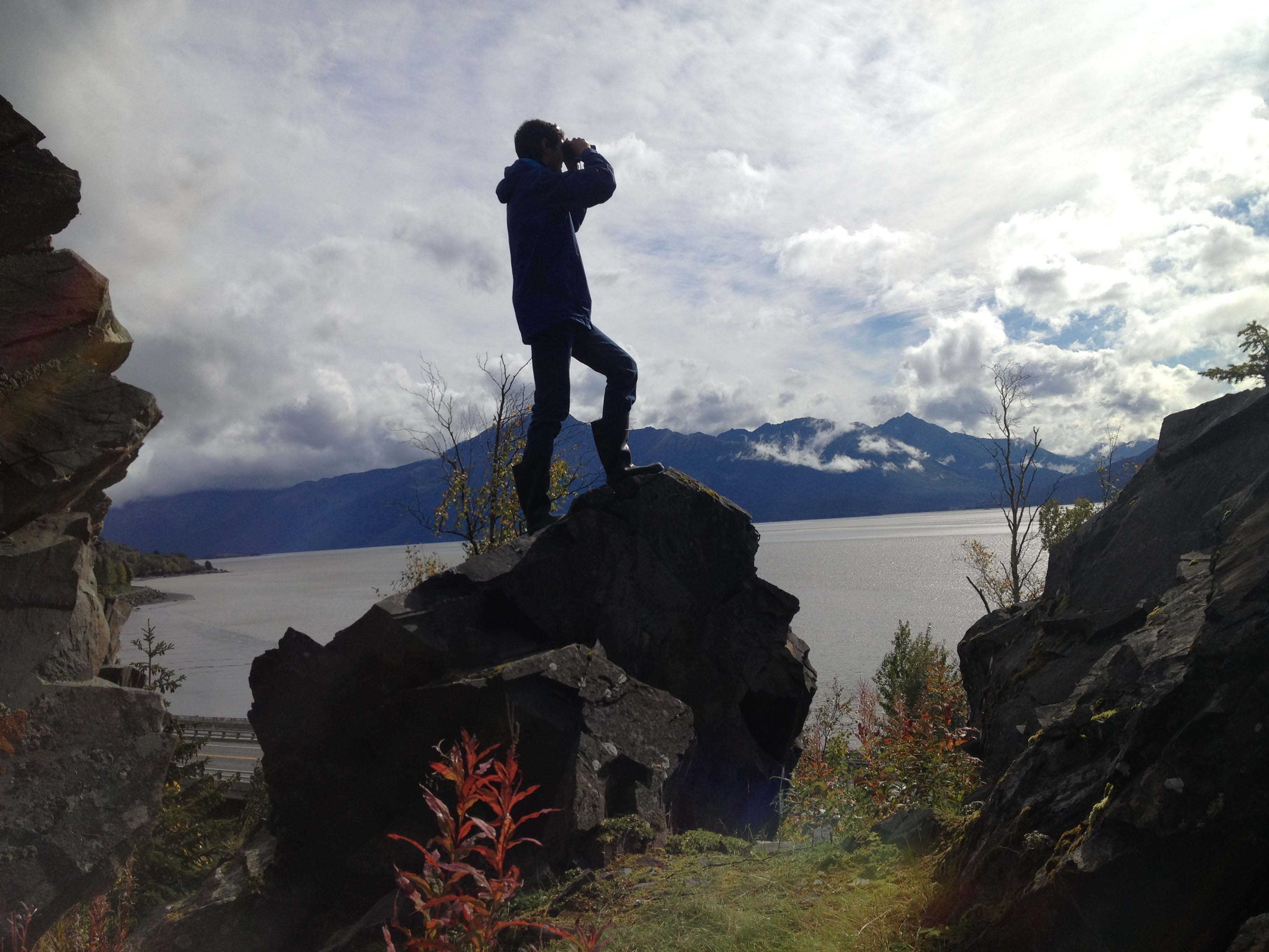 Student with binoculars gazes over cook inlet