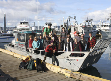 A group of students aboard a water taxi prepare for a beach cleanup