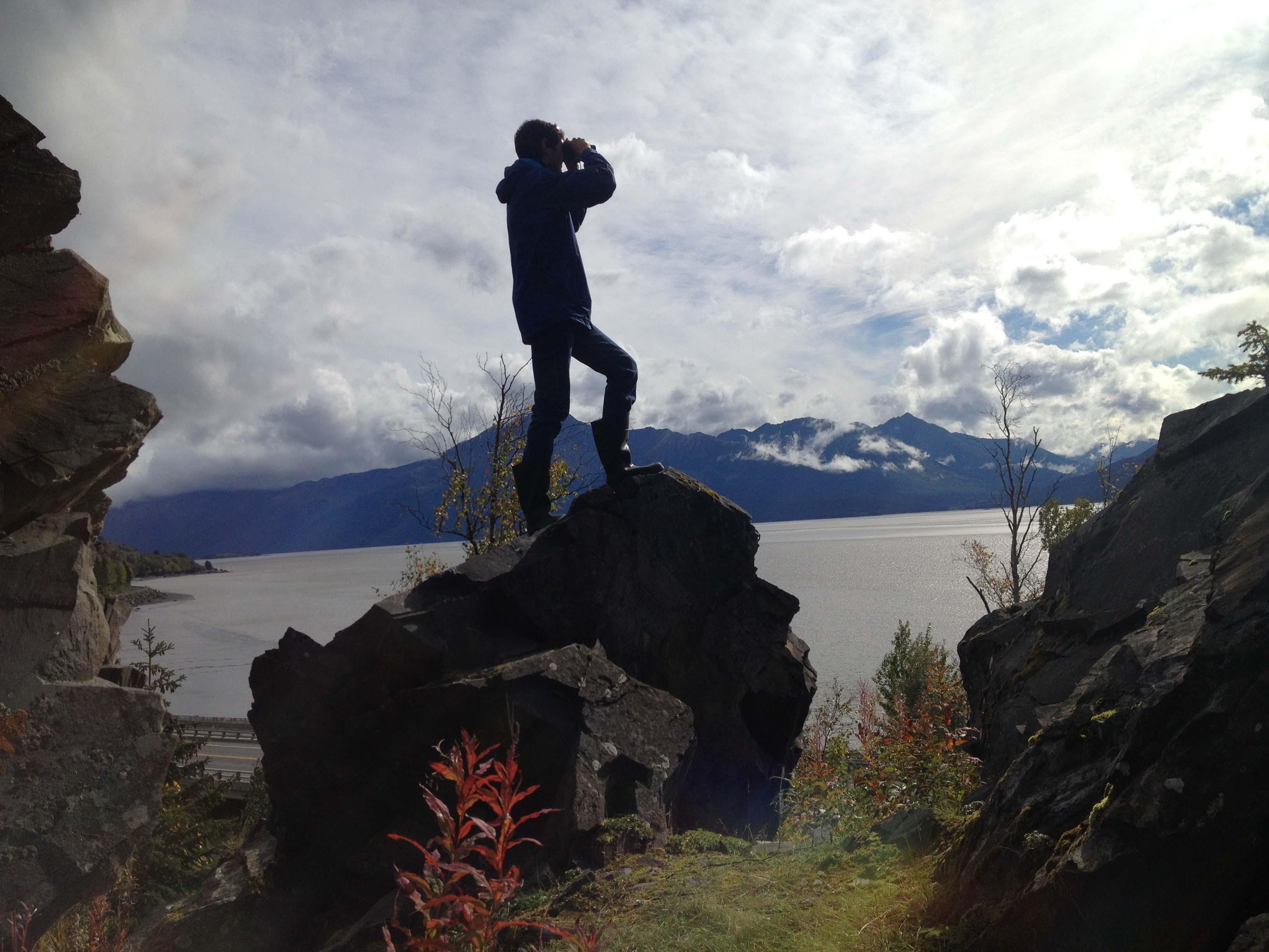 Student with binoculars gazes over cook inlet