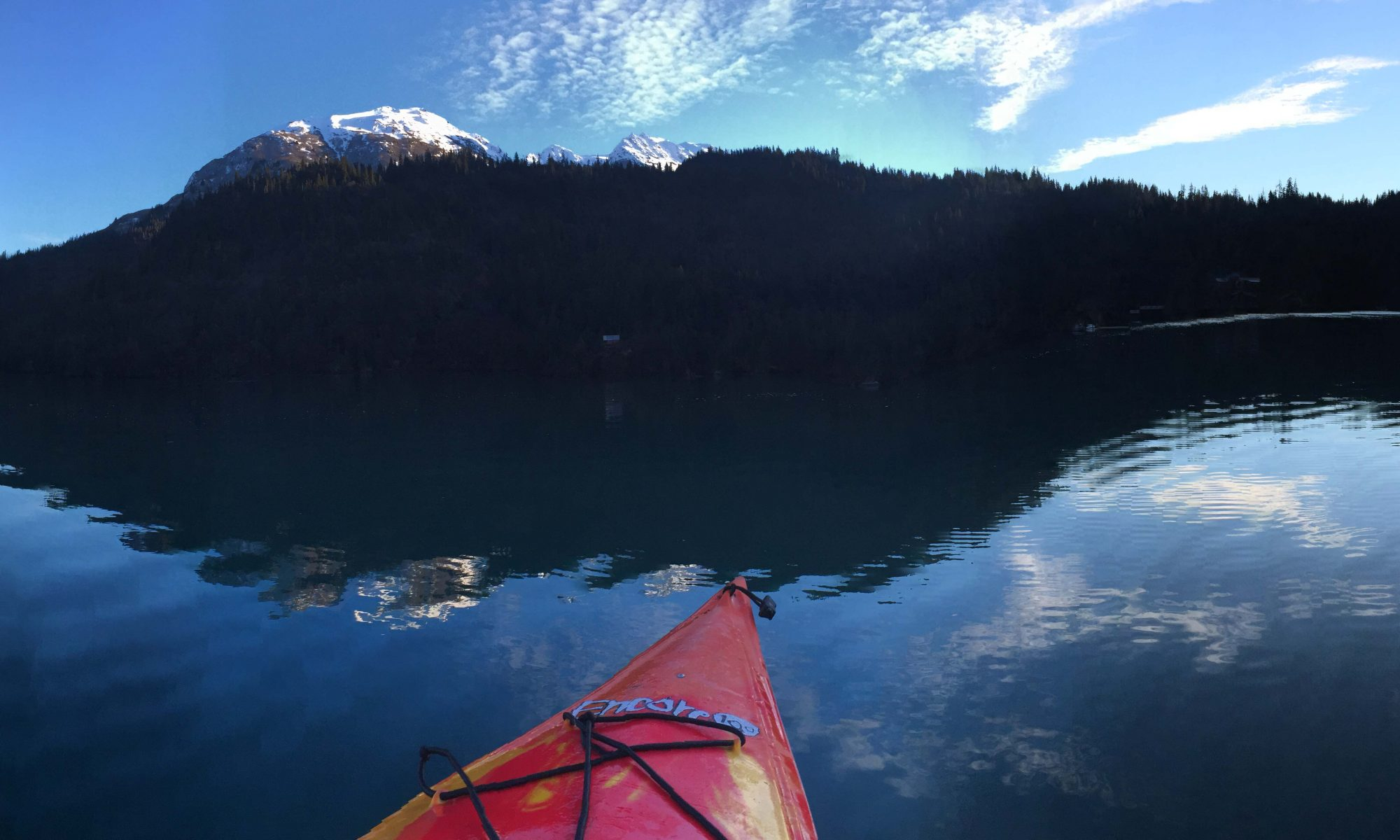 the bow of a kayak against the reflection of mountain on lake