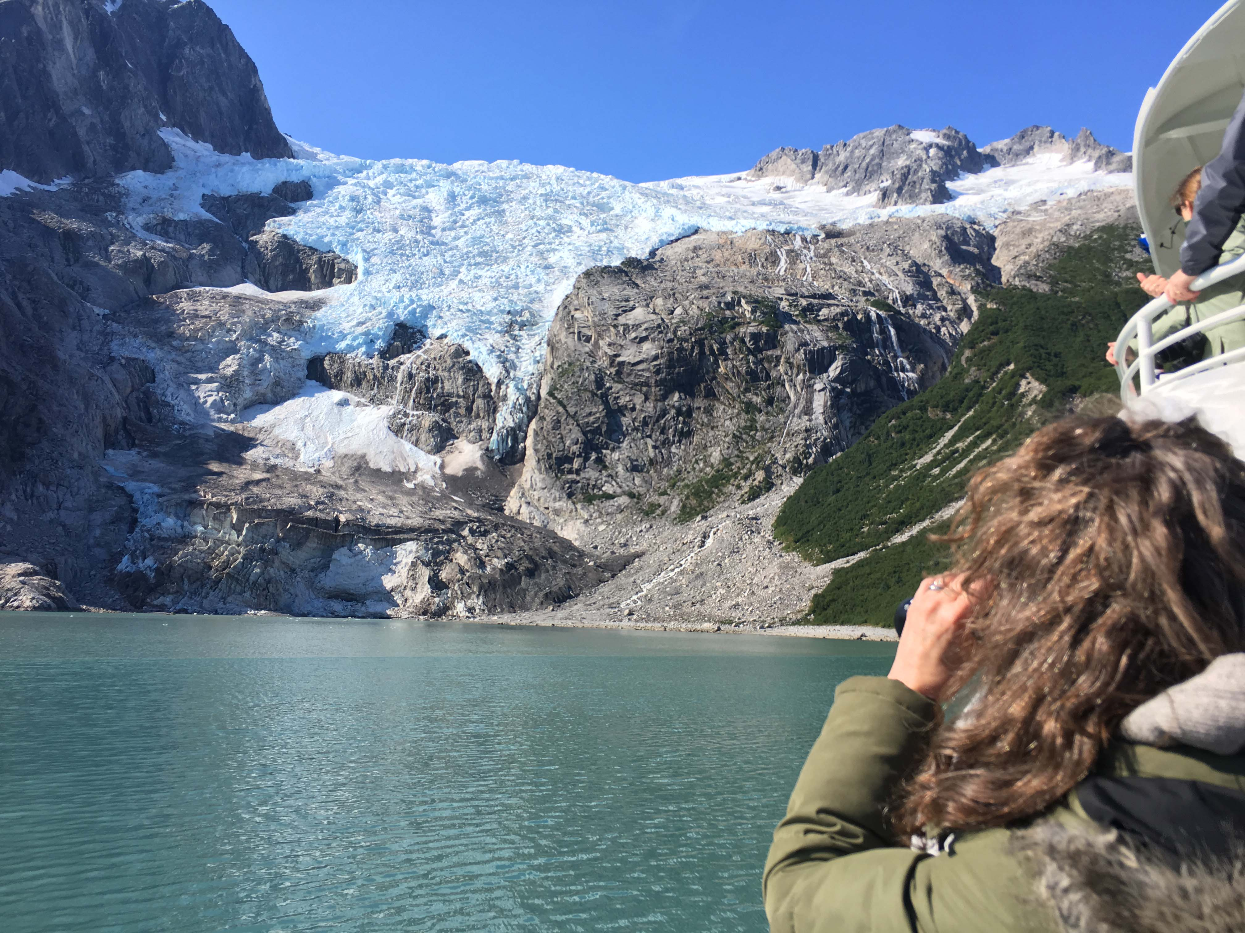 A student looks through binoculars at a looming blue glacier